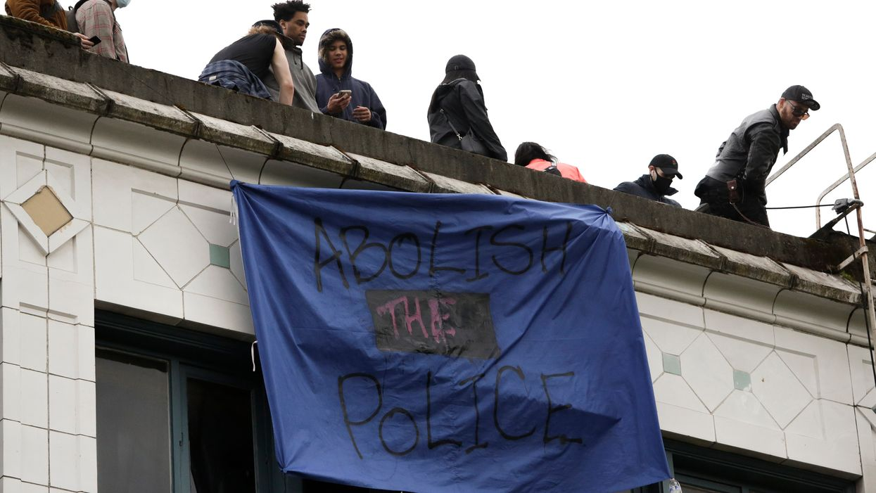 """Abolish the police"" banner hanging from the roof of a building"