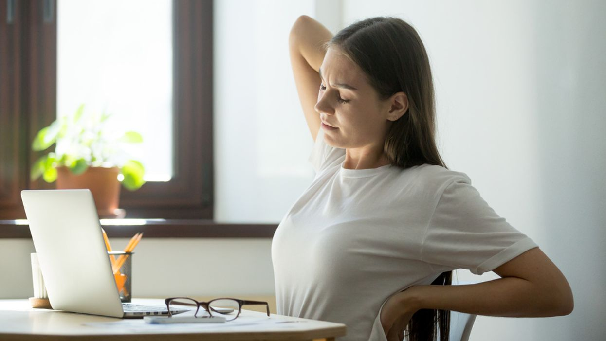 tired woman stretching at laptop
