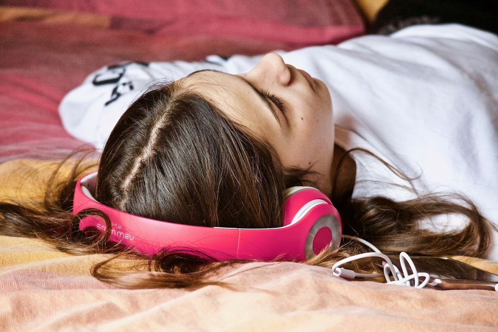 Girl laying on bed listening to music with headphones
