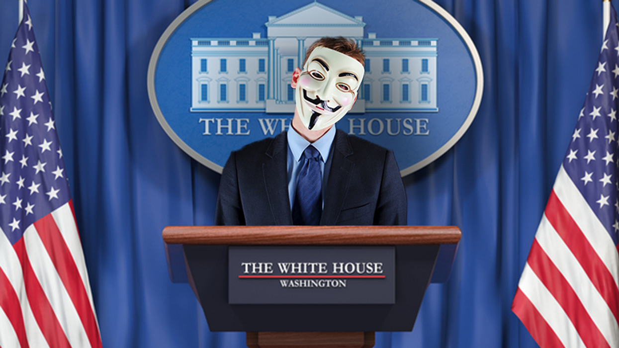 person at white house podium wearing Guy Fawkes mask