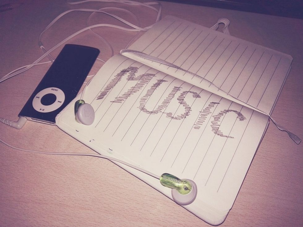 An open notebook with the word MUSIC scribbled in large letters, and an old iPod with a pair of earbuds sitting to the side.