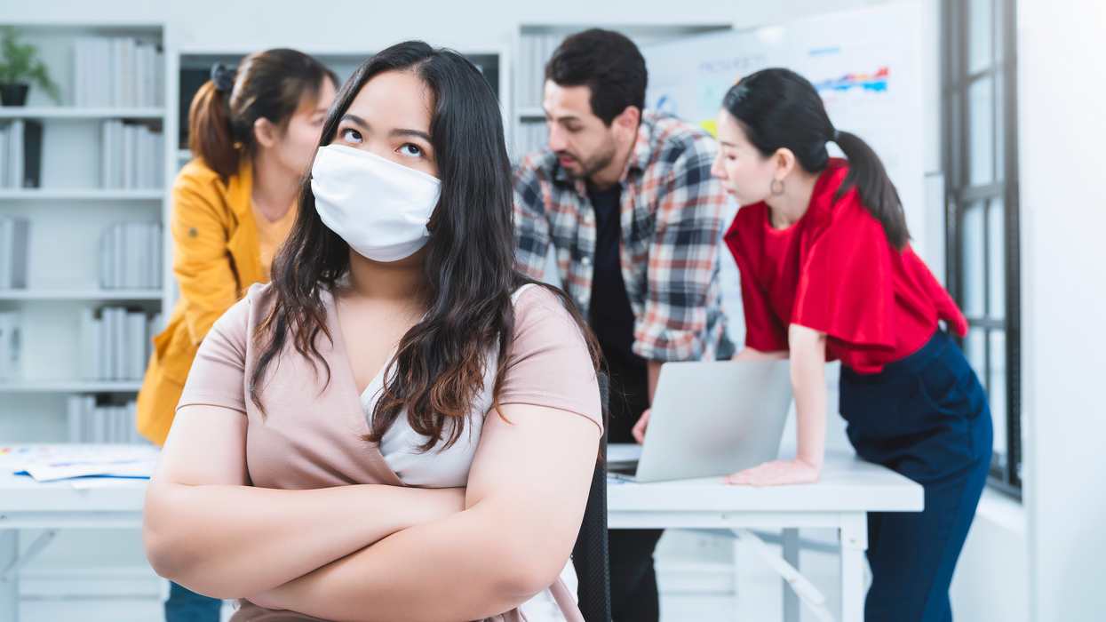 woman wearing mask with back turned to coworkers