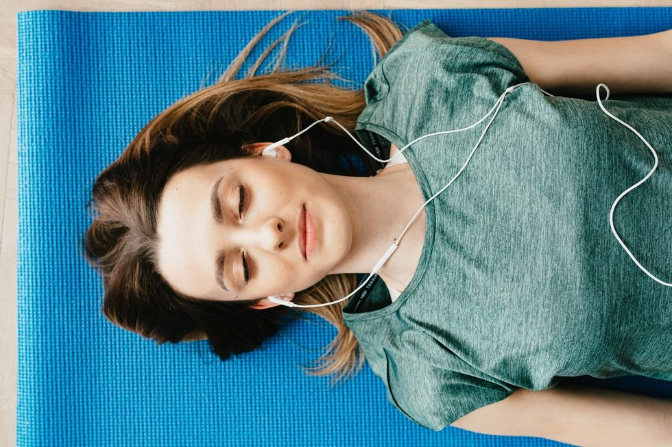 Woman listening to music laying down on yoga mat