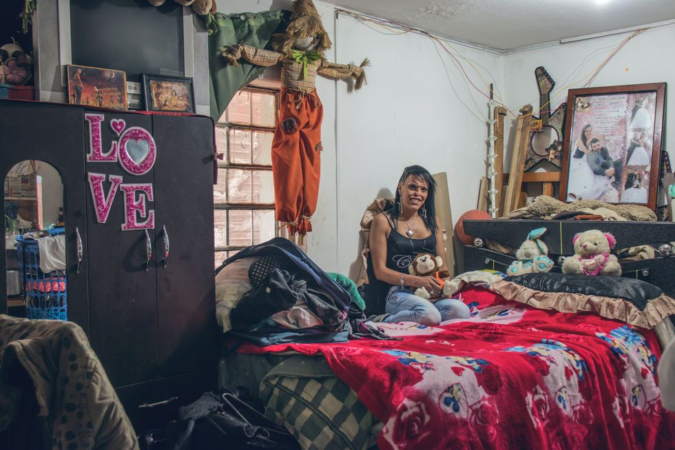 Woman on bed with stuffed animals and decorations around bedroom