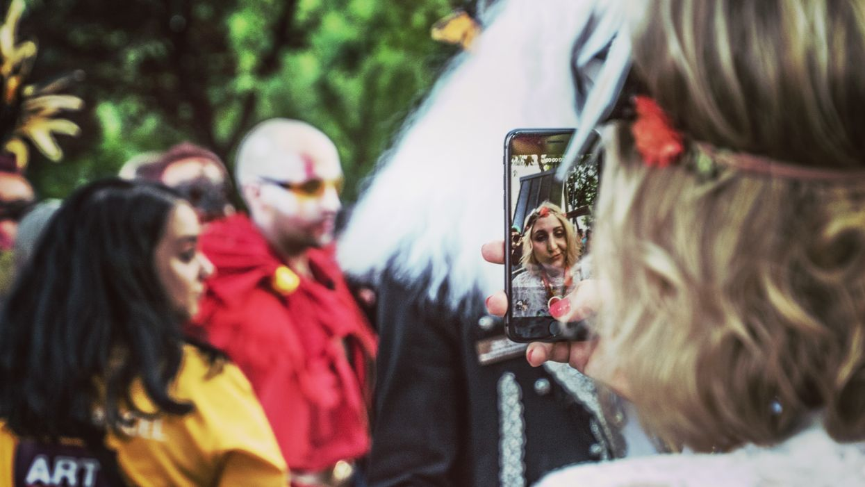 people in costume in front of woman taking selfie