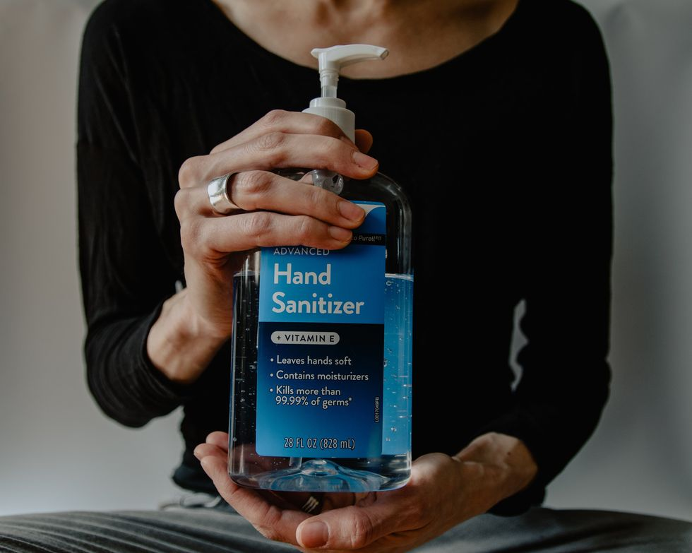woman holding bottle of hand sanitizer