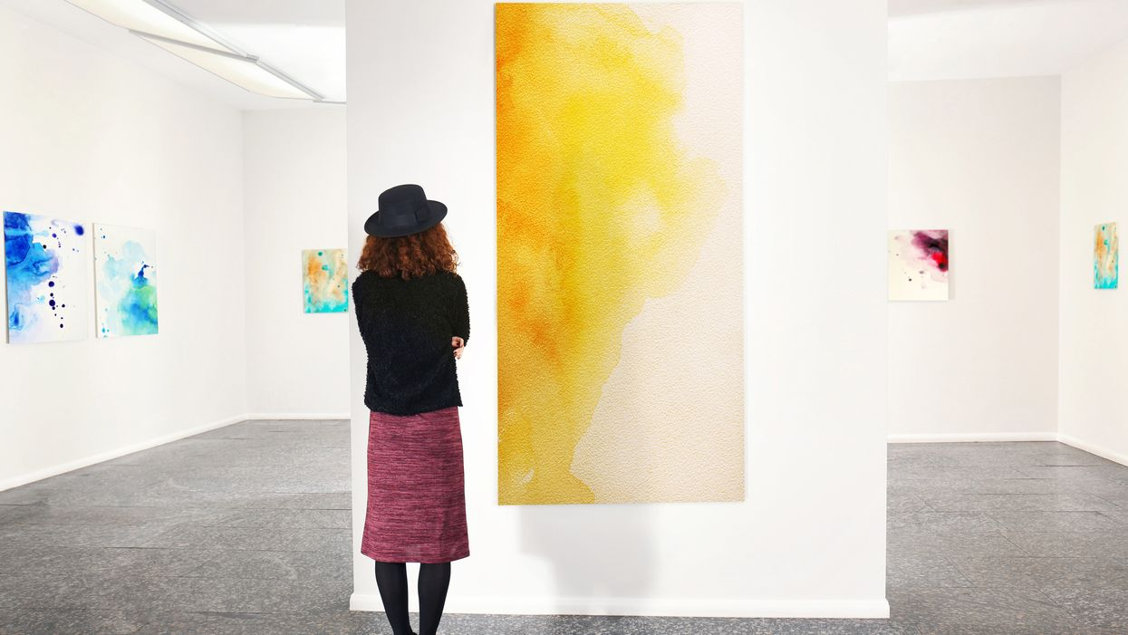 woman looking at yellow painting in gallery