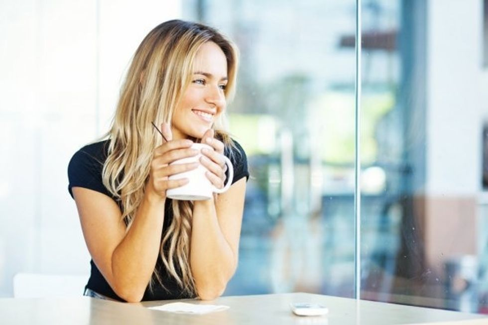 Blonde woman holding coffee in the early morning.