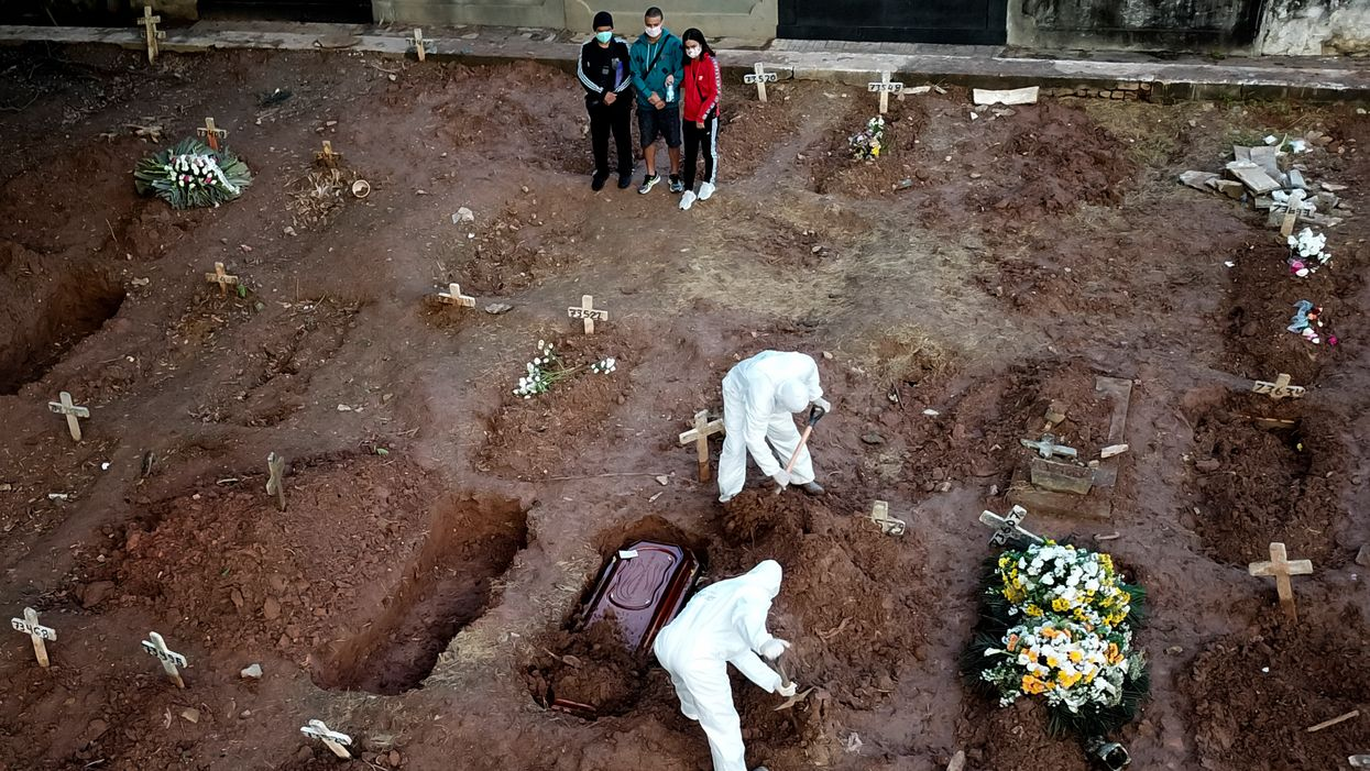 two people digging graves in white coveralls