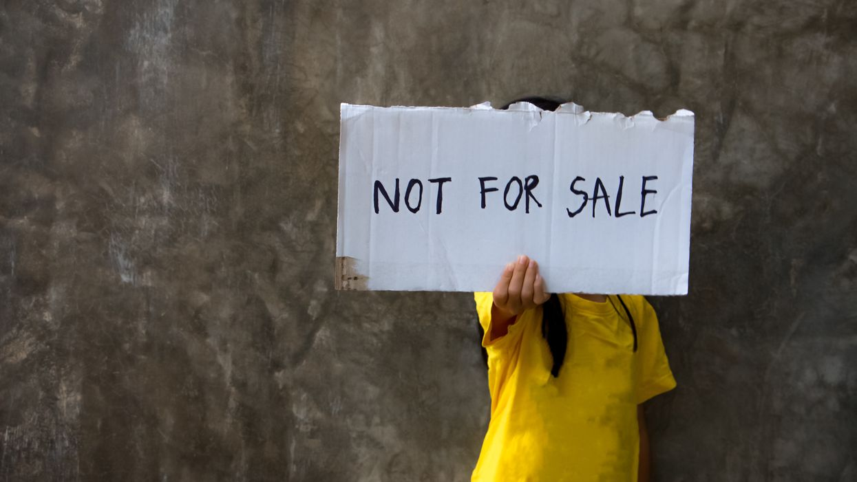 """child holding """"not for sale"""" sign"""
