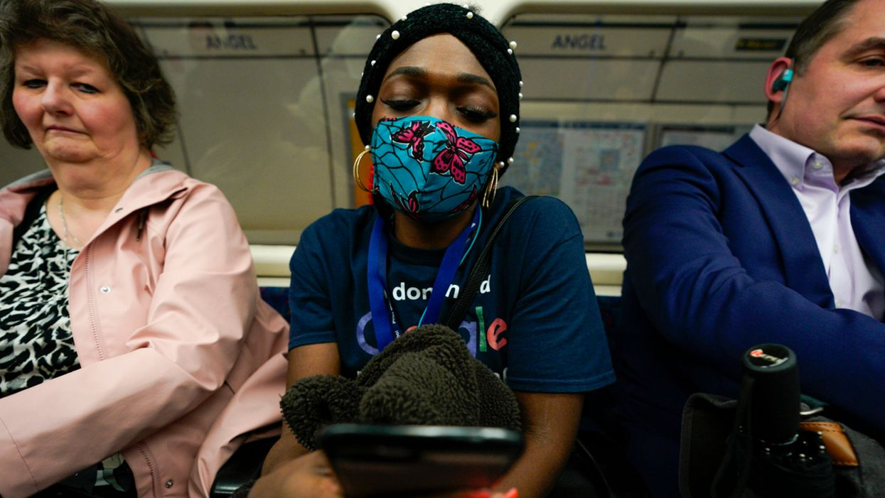 A woman wearing a homemade mask rides the London underground during COVID-19