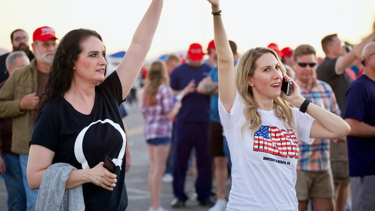 two women raising their hands at Trump rally