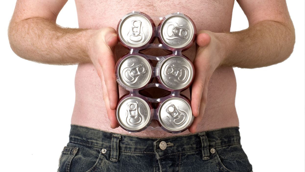 topless man holding six pack of beer