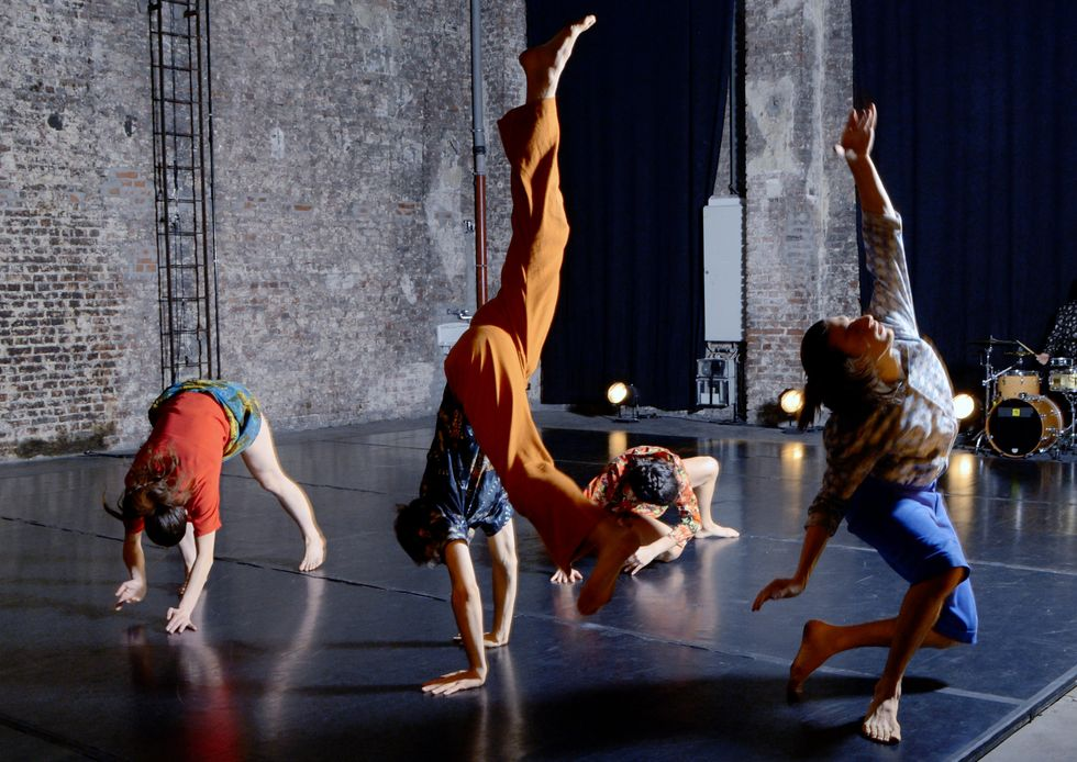 Four dancers in bright patterns and colors fall to the floor in gradual stages. One is mid-hand stand