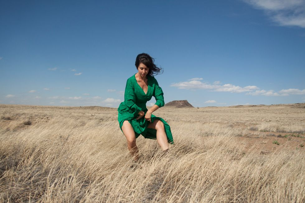 Miracle, wearing a forest green dress, dances in tall grass, a vast landscape behind her