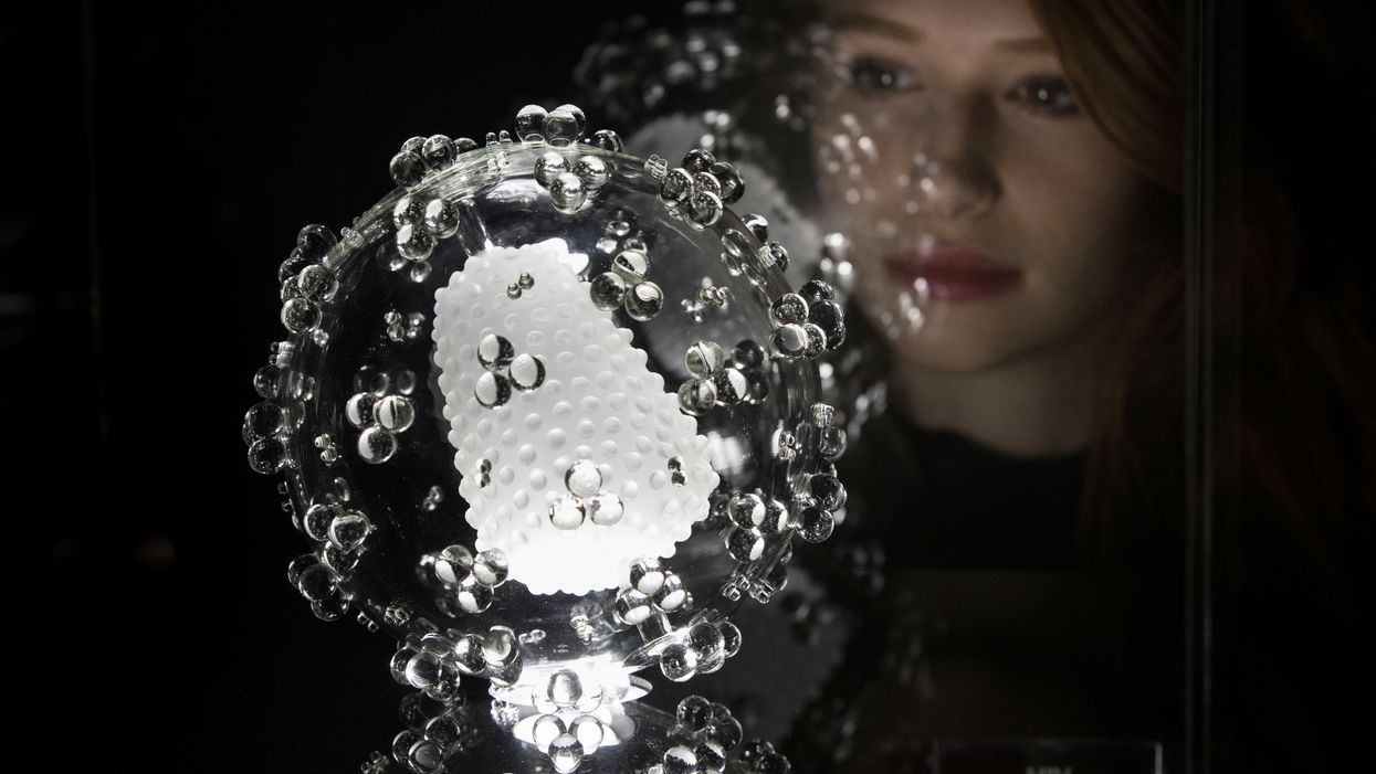A woman looks at a glass replication of a HIV cell.