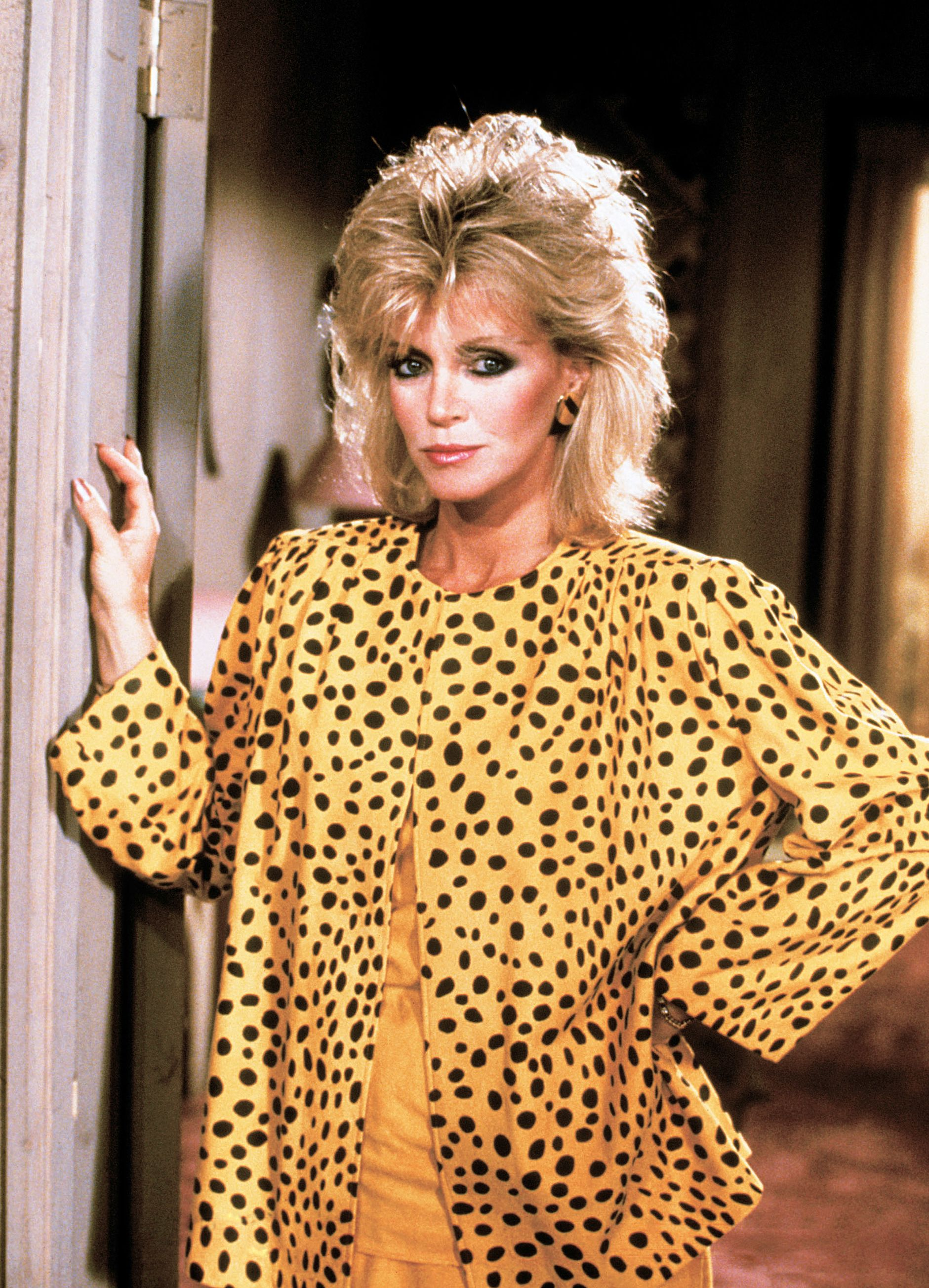 Donna Mills as Abby Ewing on the show Knots Landing wears vibrant yellow with black polka dot top with significant shoulder pads.