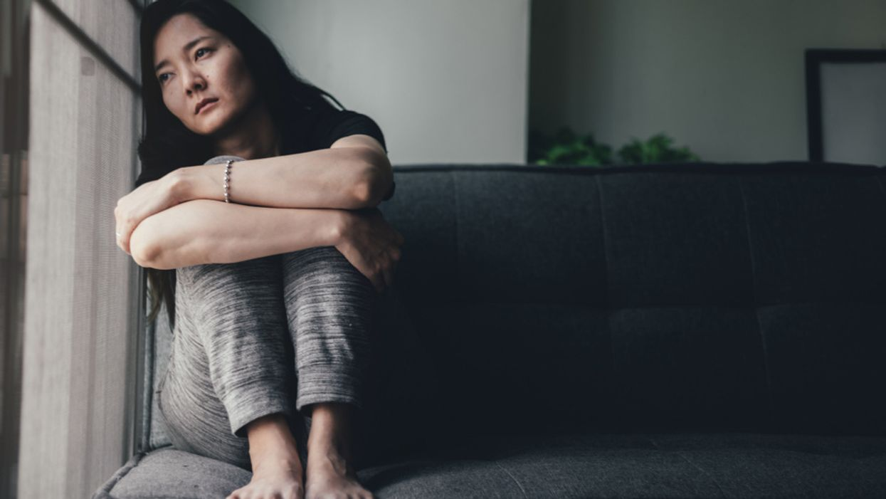 sad woman sitting alone on couch looking outside