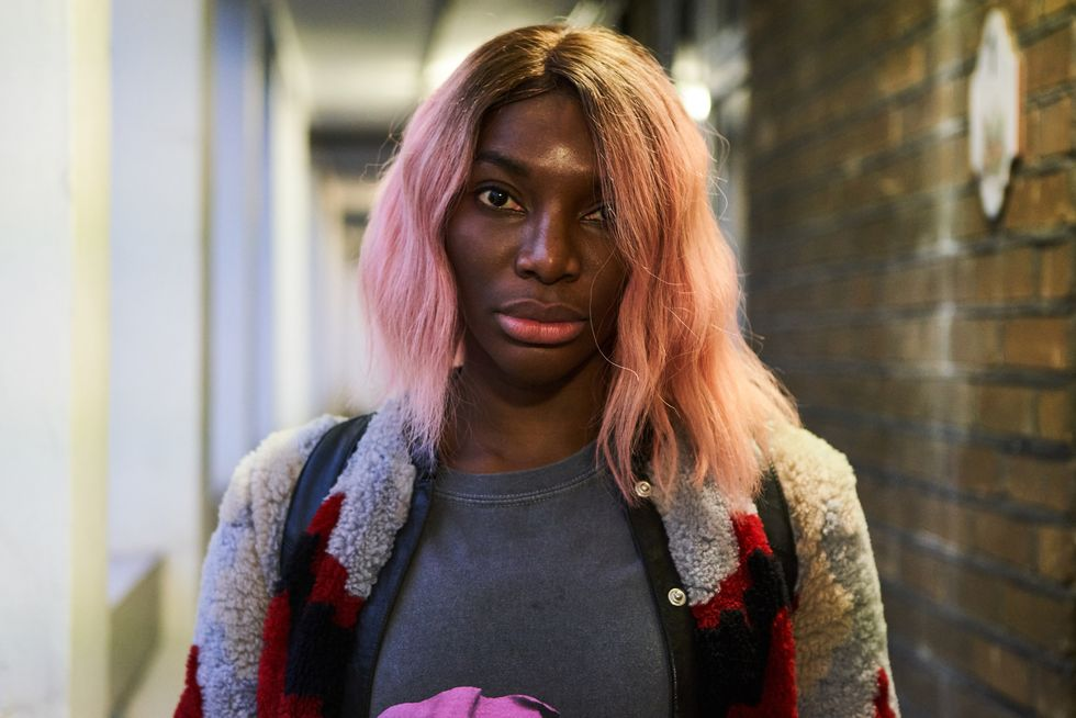 Michaela Coel in pink hair and fleece jacket looking at the camera.
