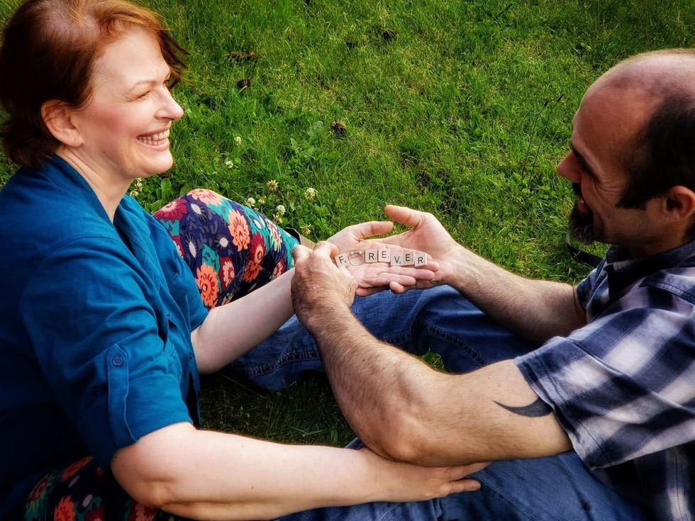"The author and her fiance sitting on the grass with the word ""forever"" spelled in Scrabble letters on her hand with her ring for the ""o"""