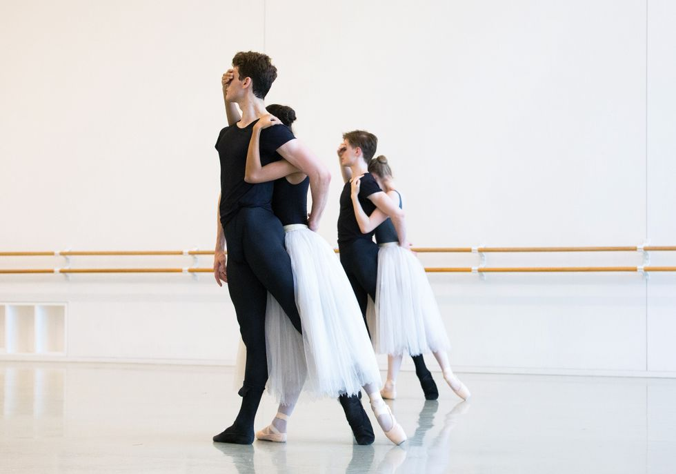 Two couples rehearse in a bright studio, The men stand in a back tendu while the two women cover their eyes and hold their shoulders from behind.