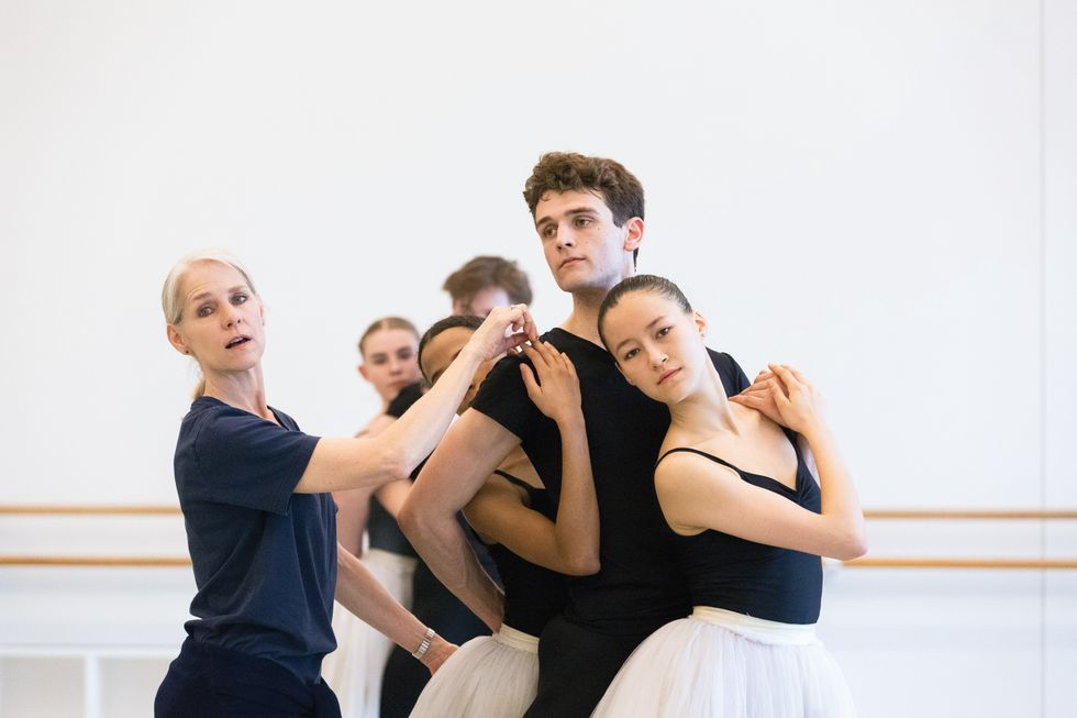 Bryant adjusts the position of a group of dancers standing in a pose in the studio.