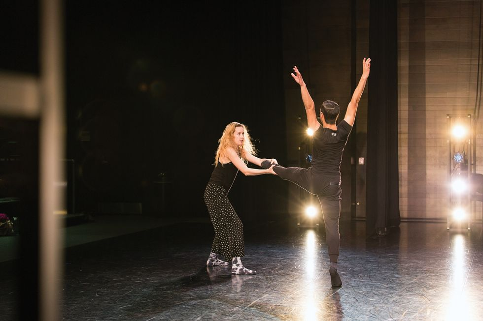 Topp holds the ankle of Panameno onstage during rehearsal, pulling him forward. He wears all black, while Topp wears polka dot pants and patterned socks.