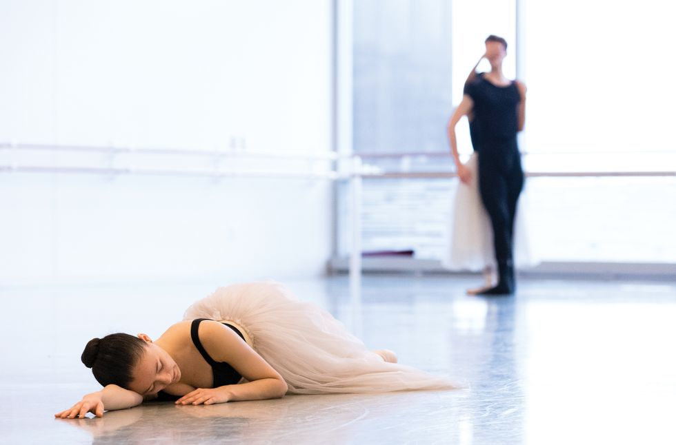 Bernard lies on the floor of a studio on her side with one arm under her cheek.