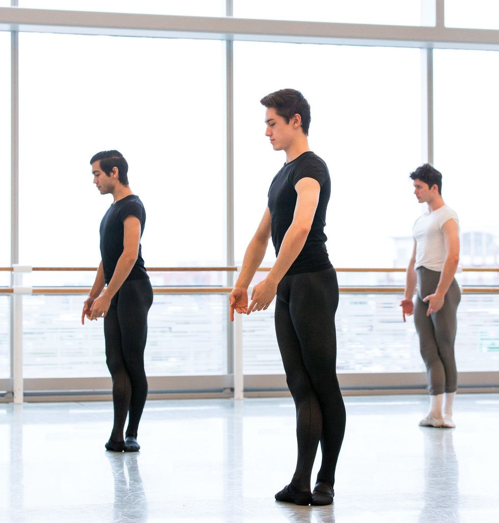 Three male students stand in fifth position in the studio with their arms in fifth en bas.