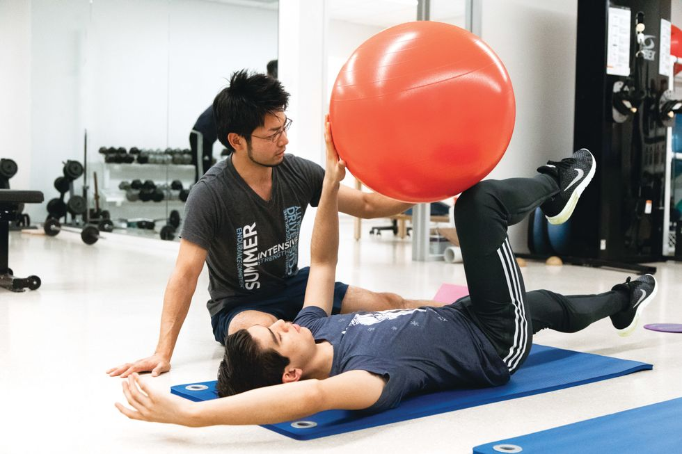 Kawasaki sits on the floor of an exercise room, guiding Panameno through a Pilates exercise on a mat with a large orange ball.