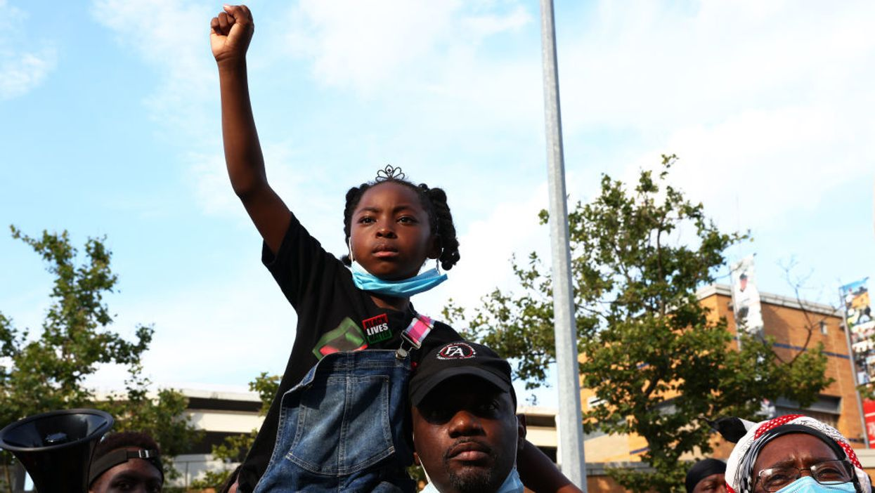 Legacy Garner, 6, the daughter of Eric Garner, raises her fist as she is held on the shoulders of Benjamin Lawton, first cousin of Eric Garner, as protesters gather in front of the 120th NYPD precinct on the sixth anniversary of Eric Garner's death in Tompkinsville, Staten Island on July 17, 2020 in New York City.