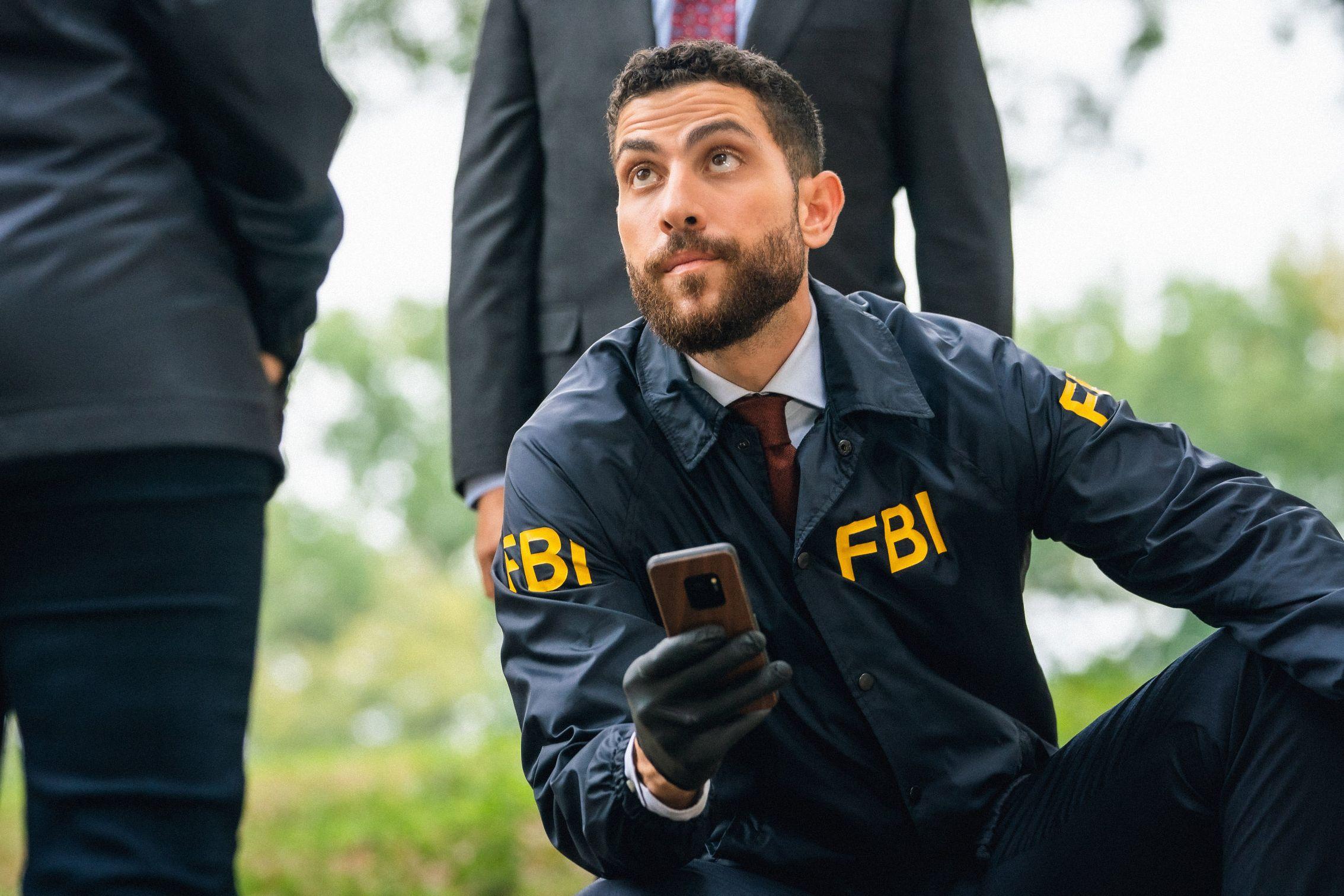 Actor Zeeko Zaki wears an FBI windbreaker while holding up a cell phone