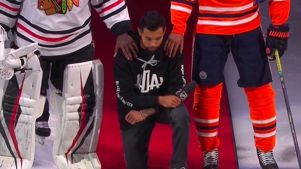 Matt Dumba kneels during the national anthem.