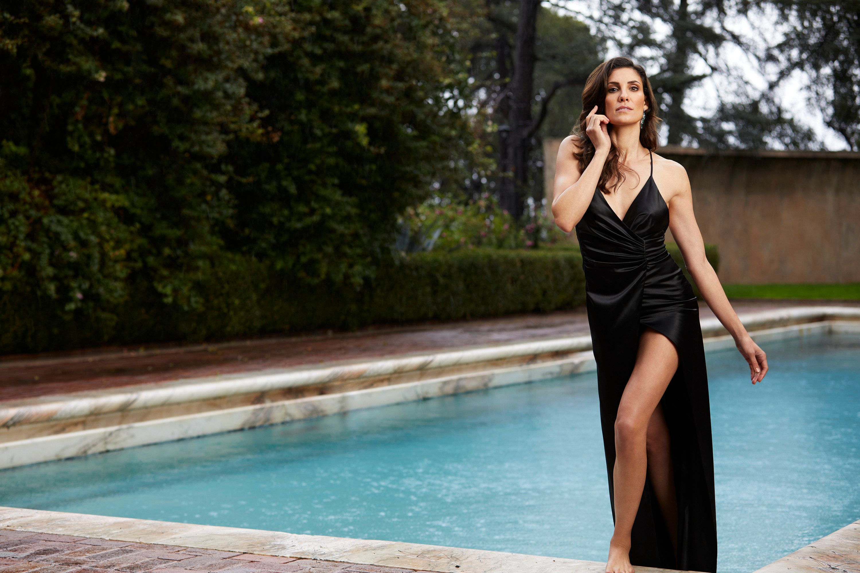 \u200bDaniela Ruah wears an elegant black evening dress as she seemingly is emerging from a swimming pool