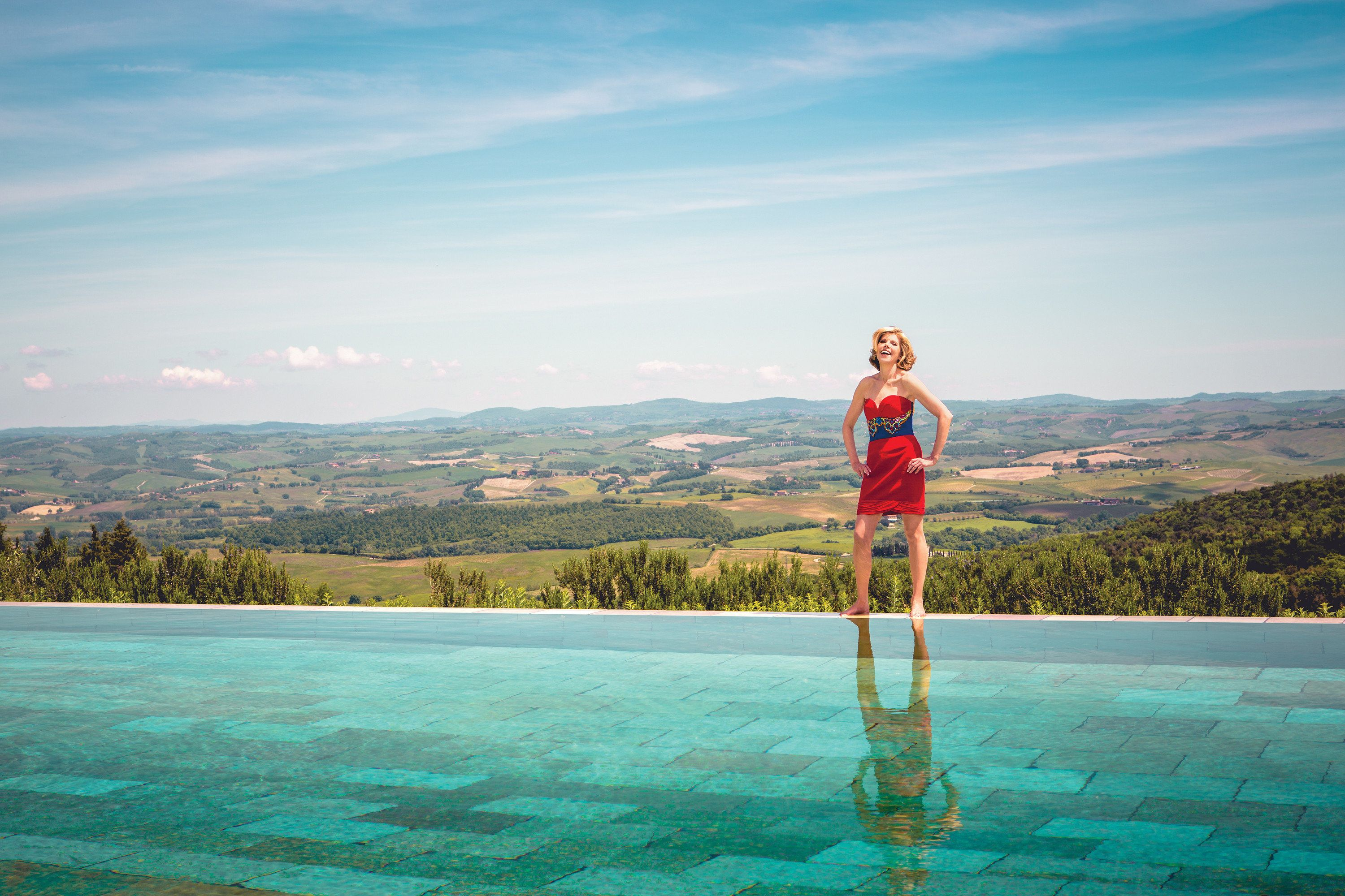 Christine Baranski stands poolside wearing a vibrant red and blue dress with a buccolic countryside stretching out behind her