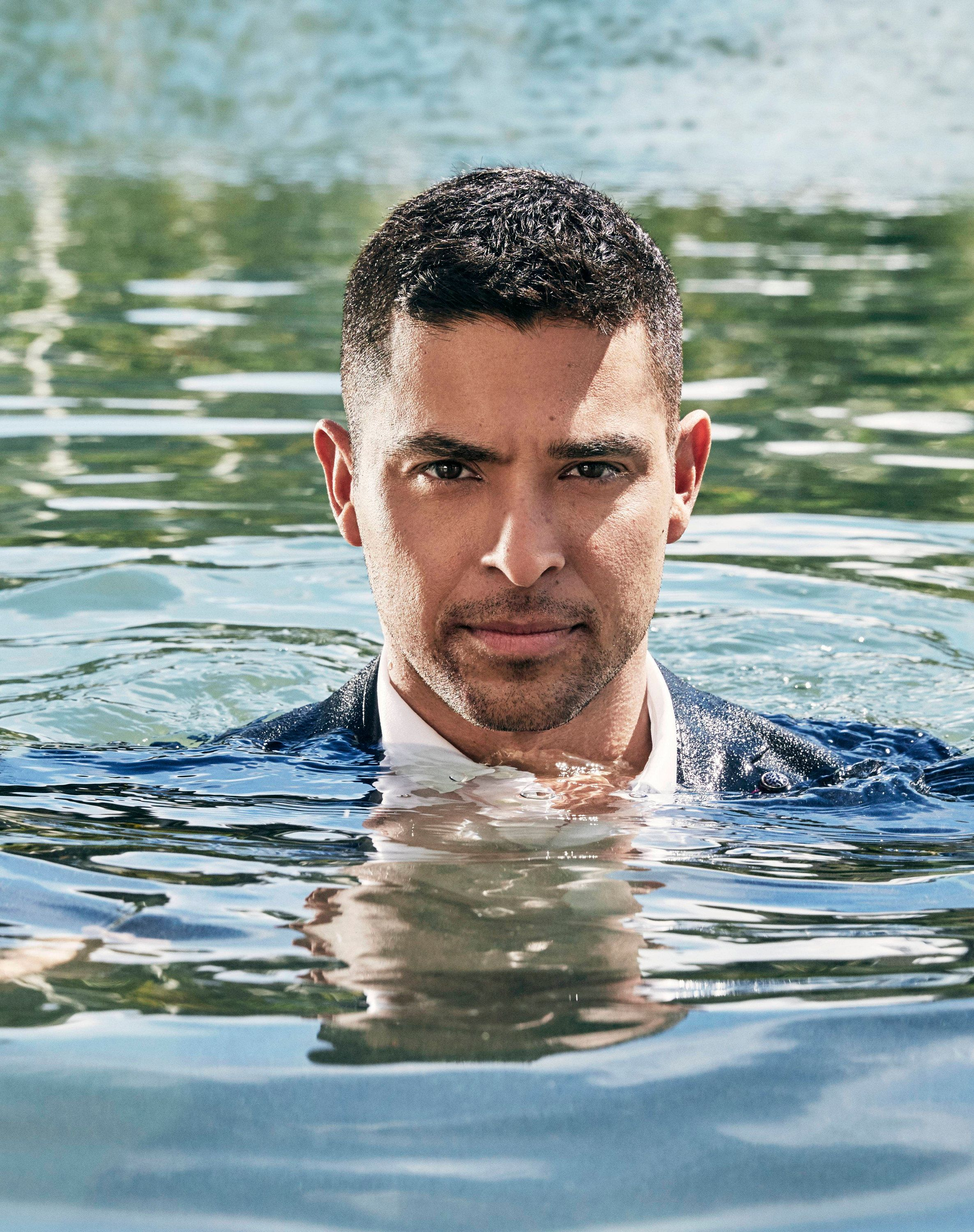 Wilmer Valderrama is fully clothed and emerging from a body of water