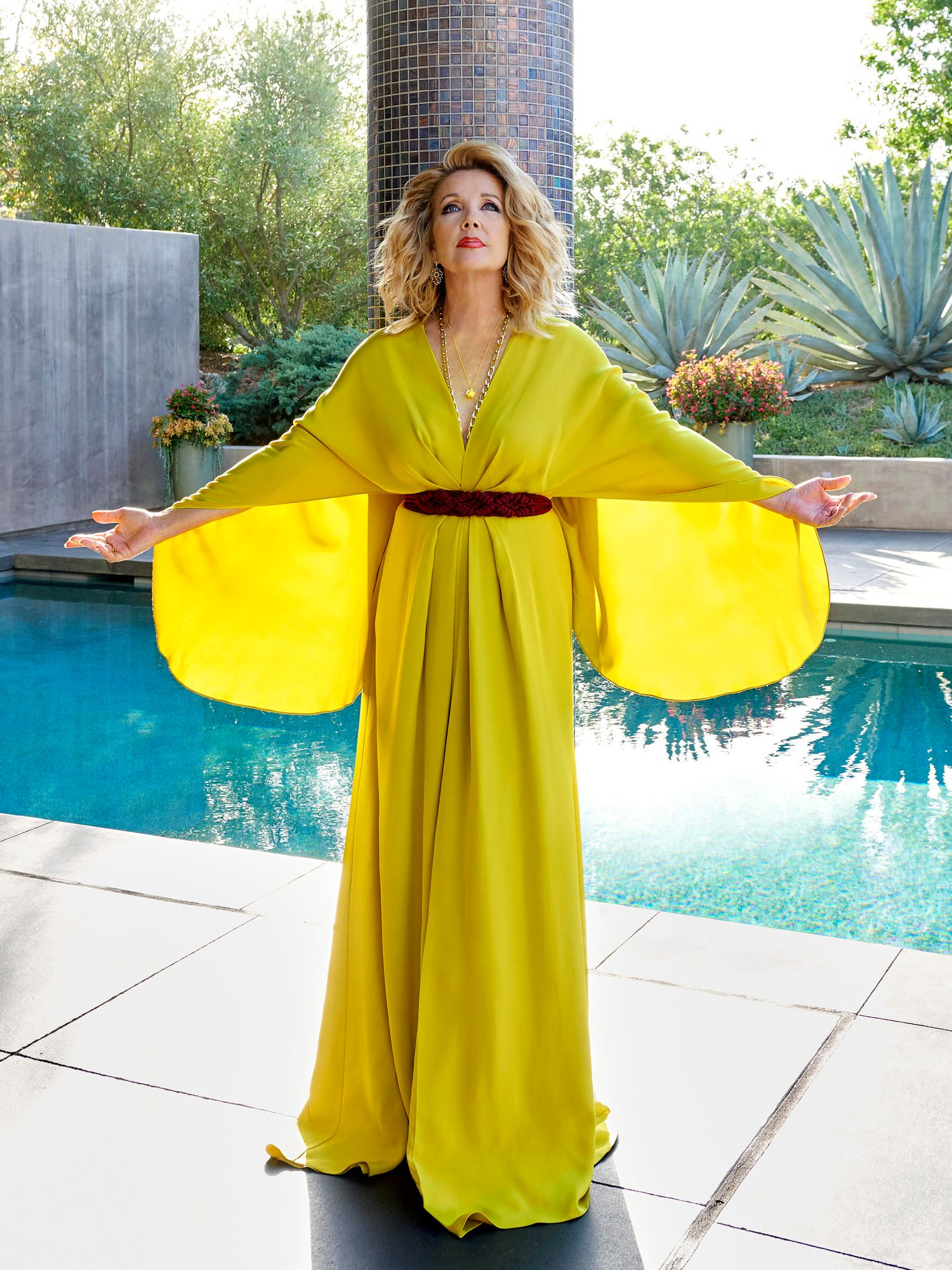 Melody Scott Thomas wears a vibrant yellow dress with massive sleeves stands in front of a pool and tiled pillar