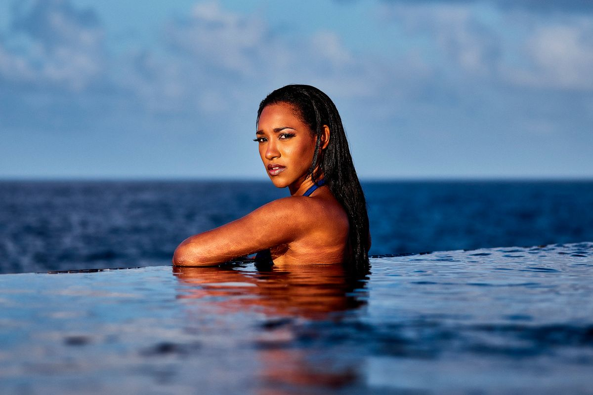 Candice Patton swims in a seaside swimming pool wearing a blue swimsuit