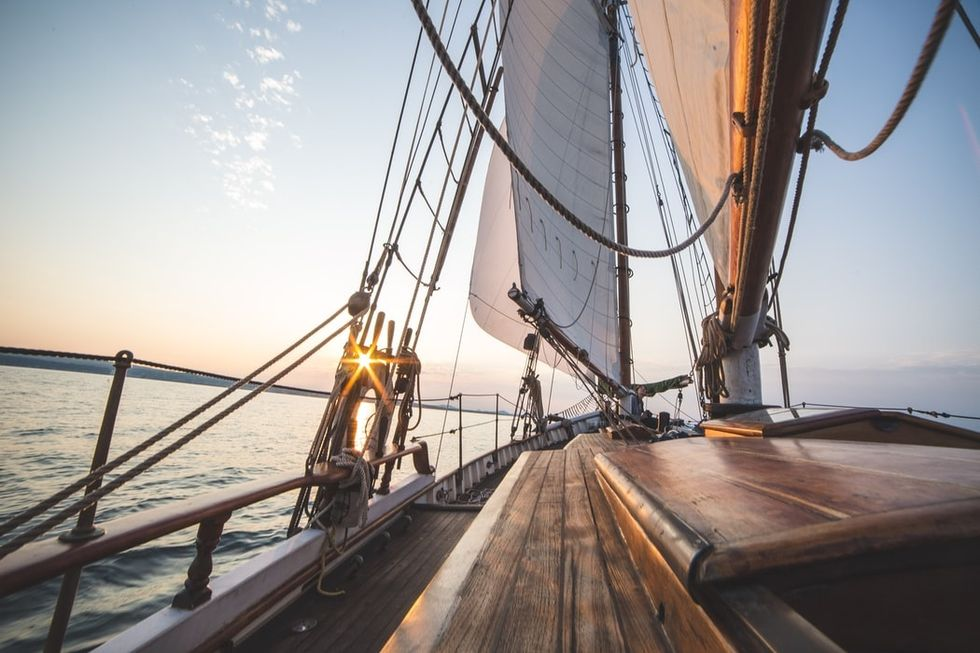 a view of the front of a wooden sailboat from the point of view of someone sitting to the left of the cockpit during sunrise.