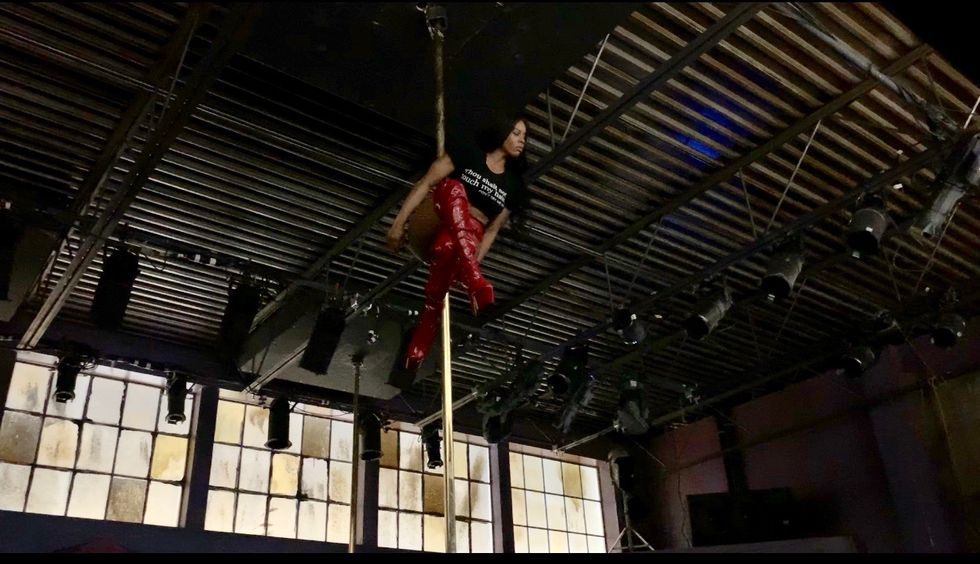 Evans clings onto a gold pole between her thighs high up in a warehouse