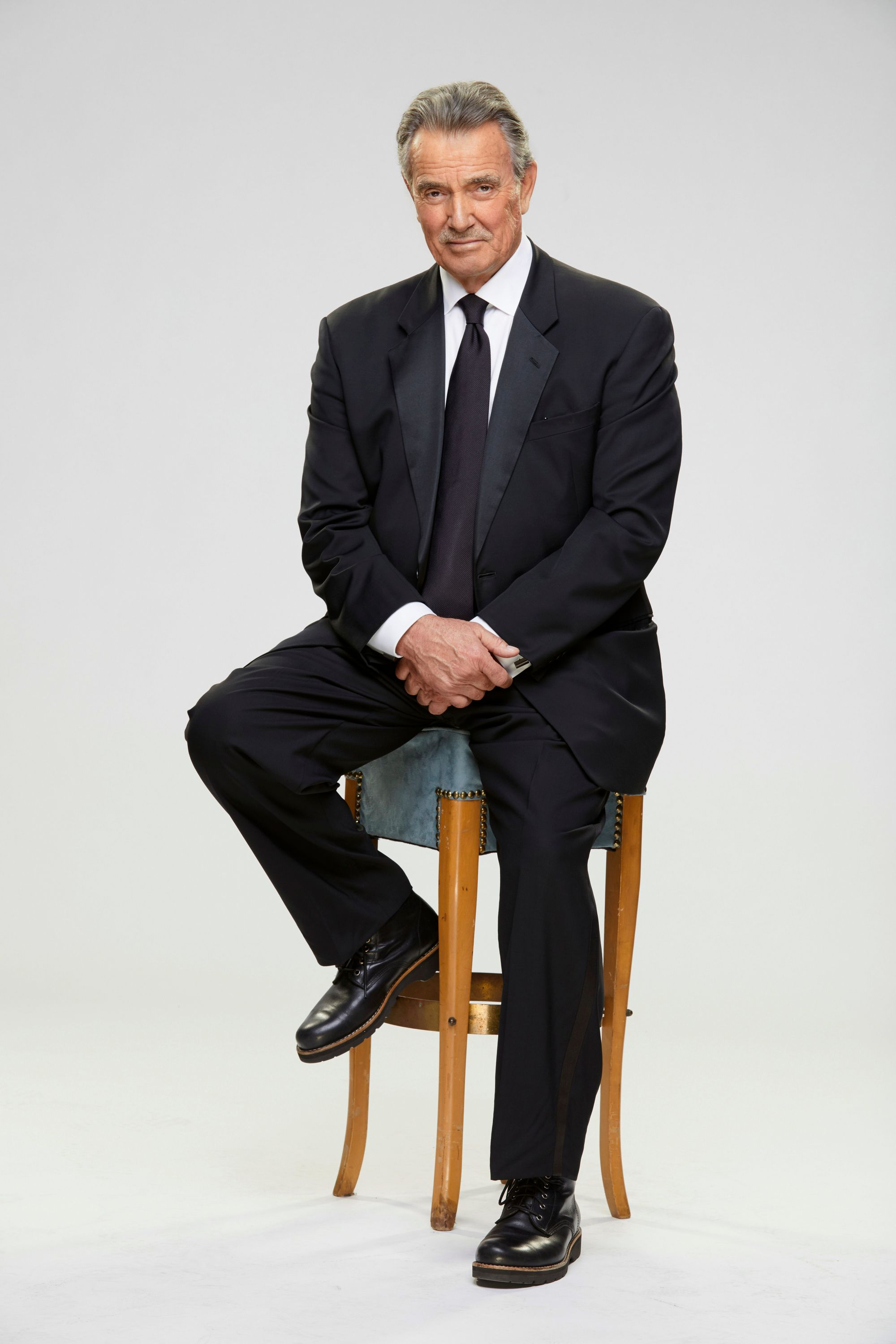 Eric Braeden as Victor Newman sitting on a stool