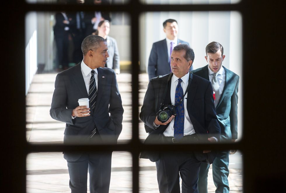 """Pete Souza (right with camera) walks side-by-side with President Barack Obama in a scene from Focus Features and MSNBC Films' documentary """"The Way I See It."""""""