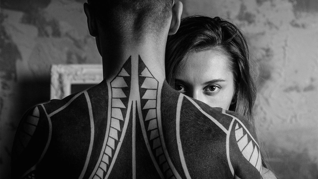 woman looking over shoulder of man with back tattoos