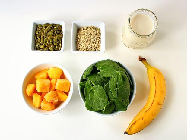 Reúna seus suprimentos: sementes de abóbora, sementes de cânhamo, amêndoa ou leite de soja (escolha soja para obter 6g de proteína a mais), banana (use congelada para obter uma textura mais espessa), espinafre bebê e pedaços de manga congelados.