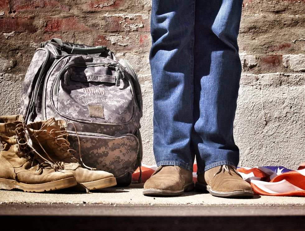 Man standing next to combat boots, military backpack and American Flag