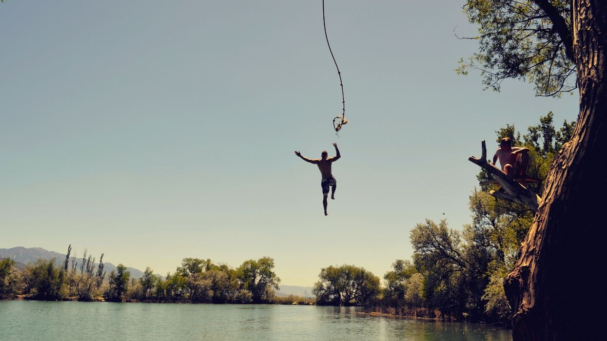 man jumping from rope swing