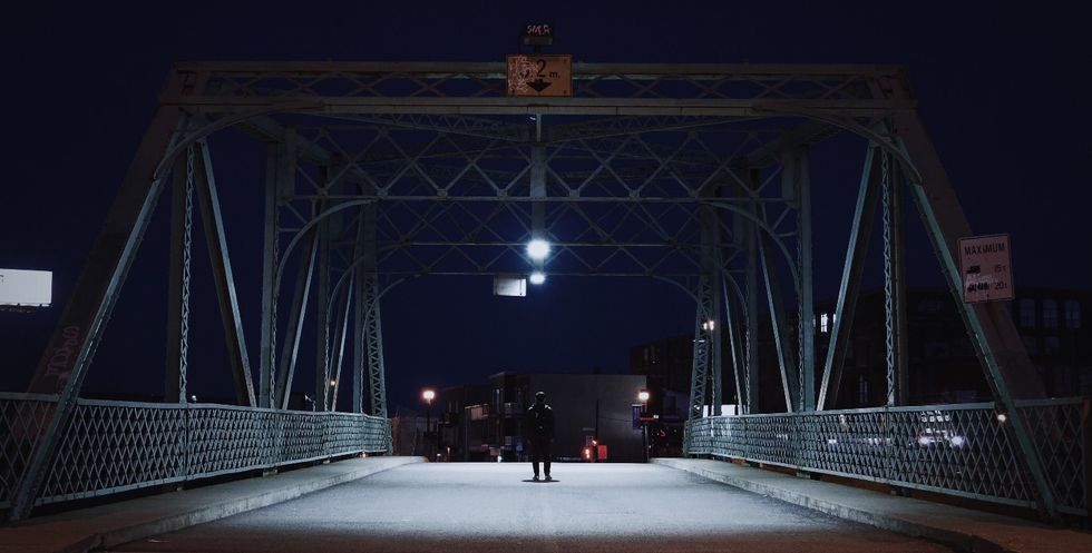 person standing on bridge at night