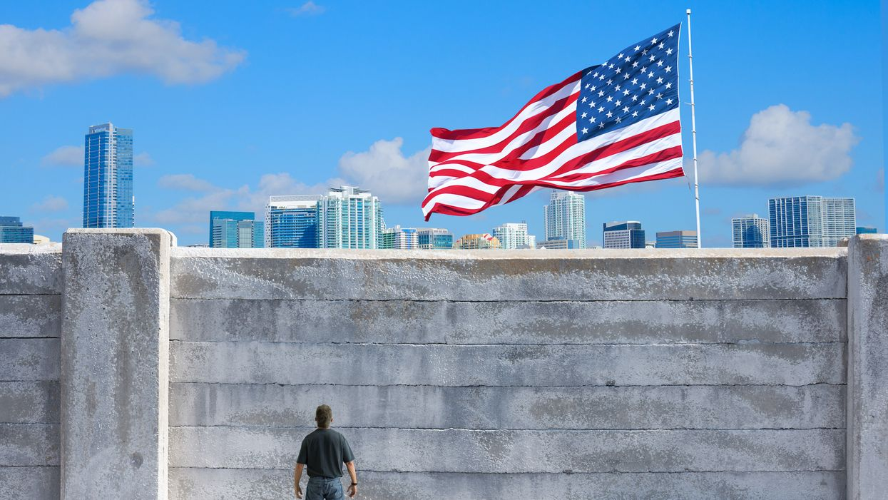 man standing at wall with American flag on other side