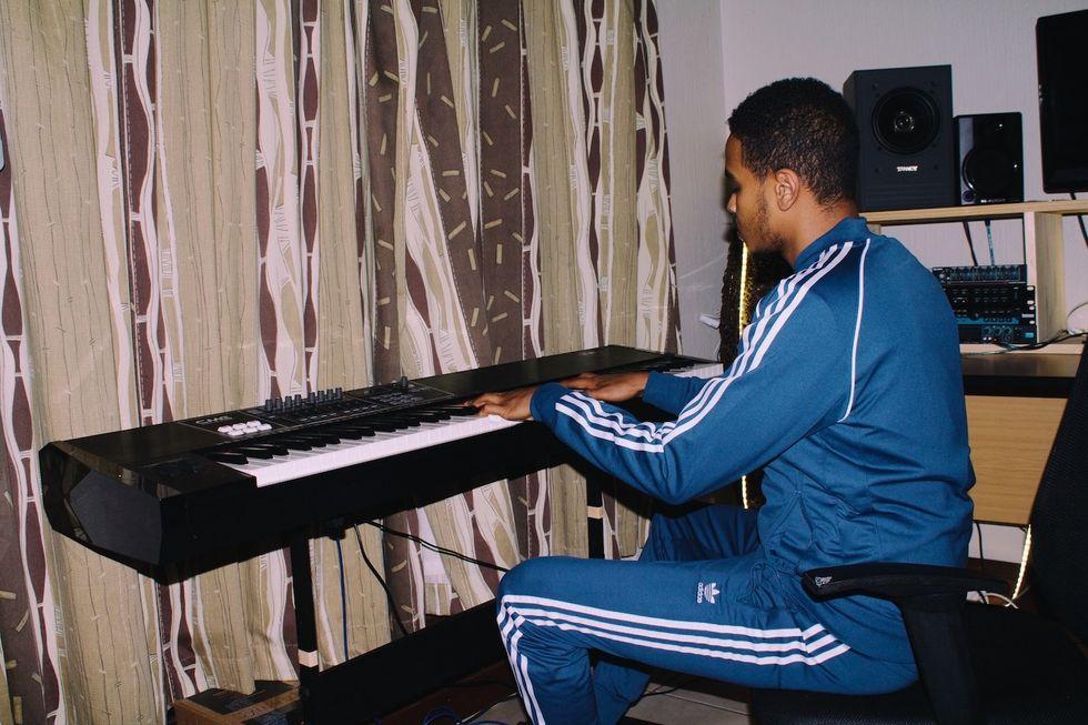 Xplosive DJ playing a keyboard in his home studio.