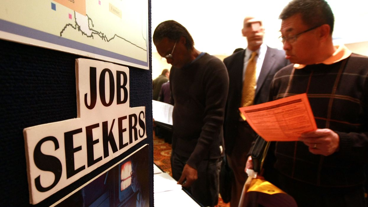 men looking at papers at job expo